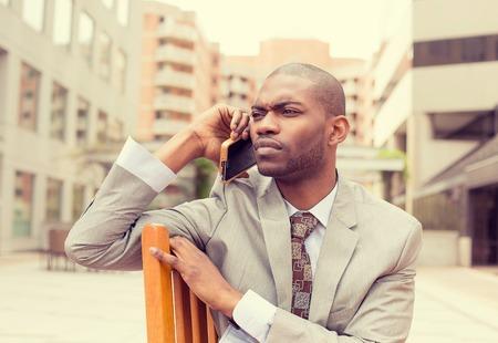 radiacion: Retrato preocupado hombre joven hablando por teléfono móvil al aire libre Foto de archivo