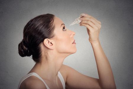 yeux: Profil de côté jeune femme appliquant eye gouttes isolé sur fond gris mur