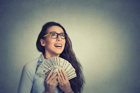 손 격리 된 회색 벽 배경에 근접 촬영 초상화 행복하고 흥분된 성공적인 젊은 비즈니스 여자 돈 달러 지폐. 긍정적 인 감정 표정 느낌. 금융 보상