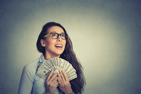 Closeup portrait happy excited successful young business woman holding money dollar bills in hand isolated grey wall background. Positive emotion facial expression feeling. Financial reward Stockfoto