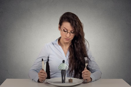 bitchy: Portrait young woman sitting at table in front of a dish looking at a tiny man isolated on gray wall background