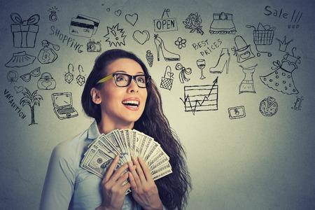 dollaro: Primo piano ritratto felice eccitato giovane donna di successo in possesso di banconote denaro dollari in mano isolato sfondo grigio muro con informazioni grafiche. Emozione positiva espressione del viso. Ricompensa finanziaria Archivio Fotografico