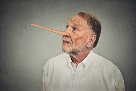 trickster: Man with long nose looking up avoiding eye contact isolated on grey wall background. Liar concept. Human face expressions, emotions, feelings. Stock Photo