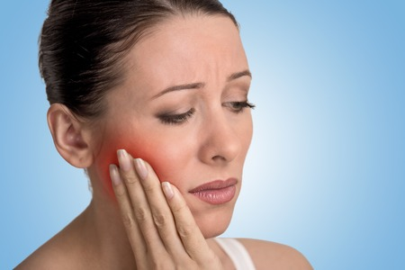 negative area: Closeup portrait young woman with sensitive tooth ache crown problem about to cry from pain touching outside mouth with red area isolated blue background. Negative emotion facial expression feeling Stock Photo