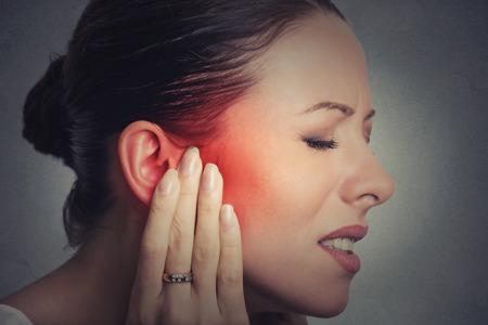 이명. 최대 근접 촬영 측면 프로필 아픈 여성 그녀의 고통스러운 머리가 회색 벽 배경에 고립 된 감동 귀 통증을 가진