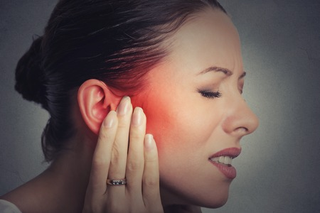 Tinnitus. Closeup up side profile sick female having ear pain touching her painful head isolated on gray wall background Stockfoto
