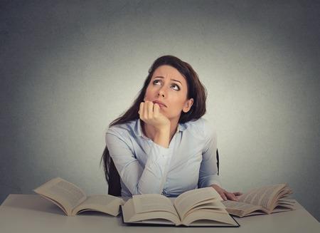 Close-up portret geïrriteerd, verveeld, moe, vrouw, grappige student zit aan bureau met vele boeken opzoeken beu bestuderen die op grijze muur achtergrond. Gezichtsuitdrukking, emotie, reactie Stockfoto