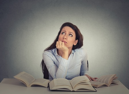 imagine a science: Closeup portrait annoyed, bored, tired, woman, funny student sitting at desk with many books looking up fed up of studying isolated on gray wall background. Face expression, emotion, reaction Stock Photo