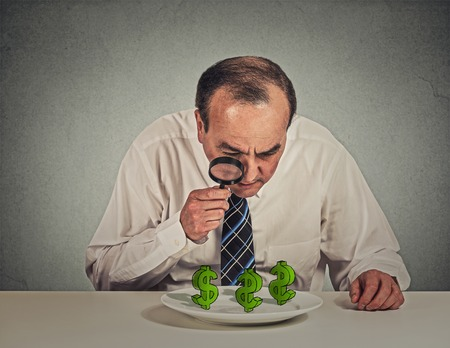dollar sign: penny pincher. Business man looking through magnifying glass at dollar signs symbol on table isolated grey wall office background. Economy financial wealth success concept. Ponzi scheme investigation