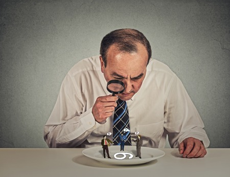 evaluating: Curious corporate businessman skeptically meeting looking at small employee standing on table plate through magnifying glass isolated grey wall background. Human face expression, attitude, perception