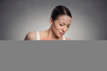 red breast: Closeup portrait young woman with breast pain touching chest colored in red isolated on gray wall background