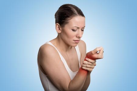 Jonge vrouw die haar pijnlijke pols over blauwe achtergrond. Verstuiking pijn locatie aangegeven door rode vlek.