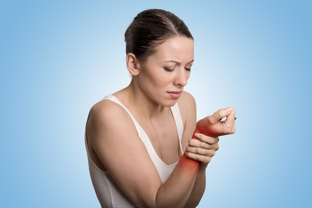 pain: Mujer joven sosteniendo su mu�eca dolorosa sobre fondo azul. La localizaci�n del dolor esguince indicado por punto rojo. Foto de archivo