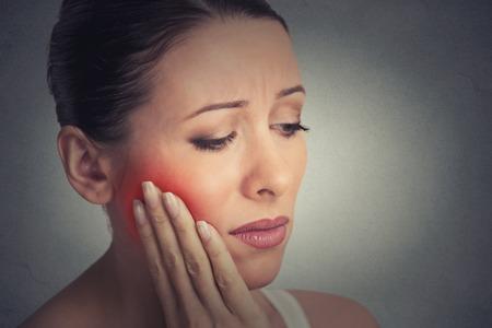 moudrost: Closeup portrét mladé ženy s citlivou zubů bolest koruny problém asi plakat od bolesti dotyku vnějšího úst rukou izolovány šedé zdi pozadí. Negativní emoce mimika pocit