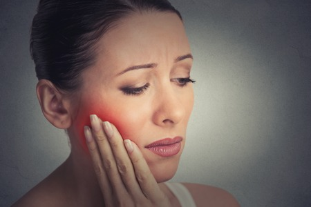 tooth root: Closeup portrait young woman with sensitive tooth ache crown problem about to cry from pain touching outside mouth with hand isolated grey wall background. Negative emotion facial expression feeling