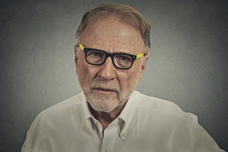Headshot portrait senior elderly skeptical man with eyeglasses isolated on gray wall background. Human face expressions, emotions, feelings, perception