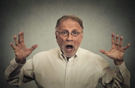 blown away: Closeup portrait shocked stunned surprised man eyes and mouth wide open, hands in air yelling screaming isolated on gray wall background. Negative human emotion facial expression feeling Stock Photo