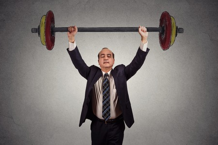 Successful business man effortlessly lifting heavy barbell isolated on gray wall background. Determination task completion hard work concept Stock Photo