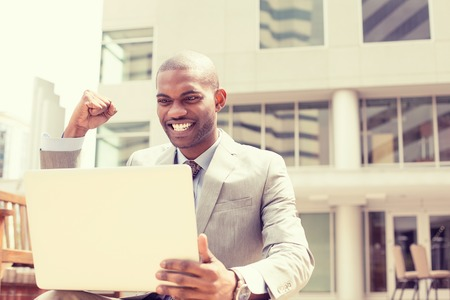 life success: Happy successful young man with laptop computer celebrates success outside corporate office Stock Photo