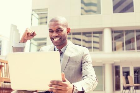 exito: Hombre joven y exitoso feliz con el ordenador portátil celebra el éxito fuera de la oficina corporativa Foto de archivo