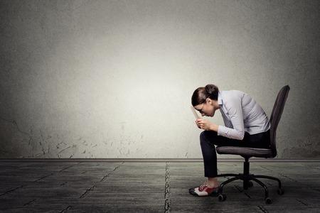 pobre: Limitaciones. Estrecha mujer corporativa mente trabajando en equipo portátil aislado sobre fondo gris pared de la oficina, con copia espacio