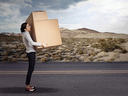 carrying heavy: Young funny looking woman carrying heavy large box package