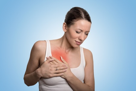 red breast: Young woman with chest breast pain colored in red isolated on blue background
