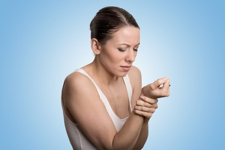 wrist pain: Young woman holding her painful wrist isolated on blue background. Sprain pain location Stock Photo