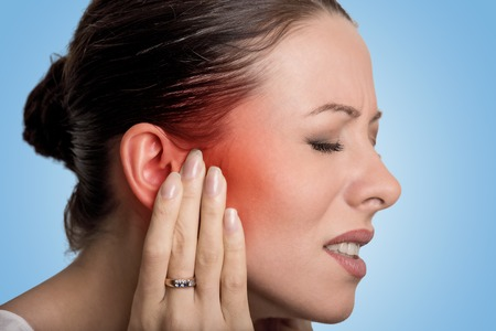 listening ear: Tinnitus. Closeup up side profile sick female having ear pain touching her painful head isolated on blue background