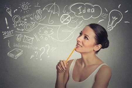 dream car: Retrato de jóvenes felices sueños mujer de pensamiento tiene muchas ideas mirando hacia arriba aislados fondo de la pared gris. Positivo expresión de la cara percepción sentimiento emoción la vida humana. Toma de decisiones concepto de proceso. Foto de archivo