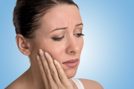 dental plaque: Closeup portrait young woman with sensitive tooth ache crown problem about to cry from pain touching outside mouth with hand isolated on blue background. Negative emotion facial expression feeling Stock Photo