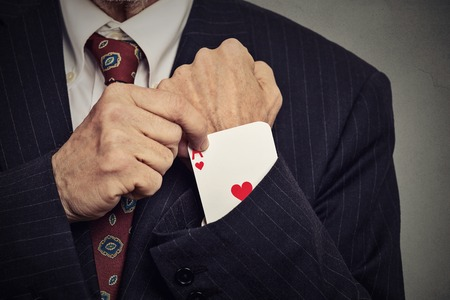 cropped image: Closeup cropped image senior man hand pulling out a hidden ace from the sleeve isolated on gray wall background