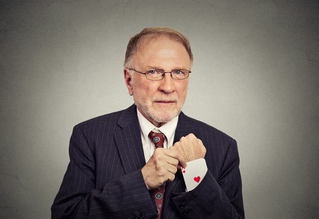 conman: Closeup portrait senior man deal maker pulling out a hidden ace card from the suit jacket sleeve isolated on gray wall background