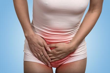salud sexual: Cerrar una imagen recortada de una mujer con las manos sosteniendo su entrepierna baja del abdomen aislado en fondo azul