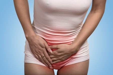 sexuel: Close up image recadrée d'une femme avec les mains tenant son entrejambe bas de l'abdomen isolé sur fond bleu Banque d'images