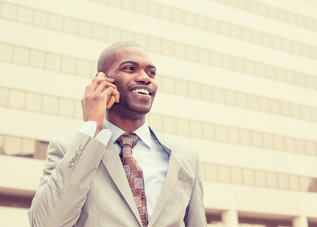 appreciating: Portrait businessman talking on cell phone outside on a background of corporate office