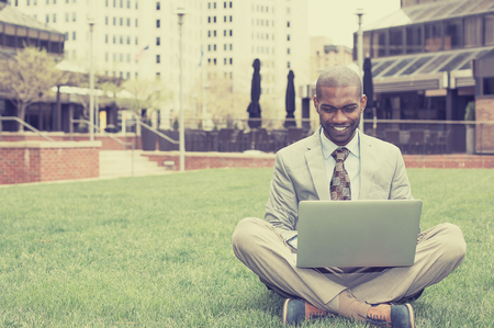 Handsome happy young businessman working with laptop sitting on meadow green grass outdoors. Stock Photo