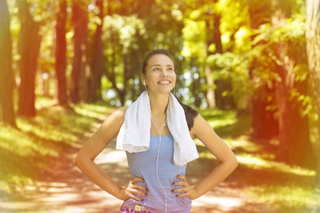 Portrait young attractive smiling fit woman with white towel resting after workout sport exercises outdoors on a background of park trees. Healthy lifestyle well being wellness concept
