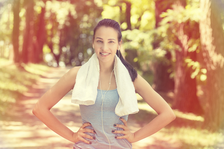 active lifestyle: Portrait young attractive smiling fit woman with white towel resting after workout sport exercises outdoors on a background of park trees. Healthy lifestyle well being wellness concept