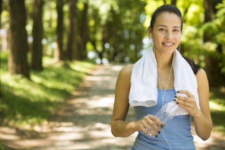 Portrait young happy attractive smiling fit woman with white towel resting after sport exercises outdoors on a background of park trees. Healthy lifestyle well being wellness concept 版權商用圖片 - 42175059