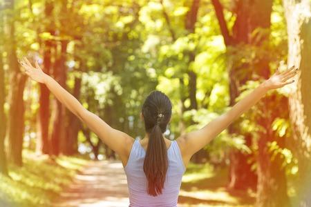 Giovane donna alzò le braccia fino al cielo, celebrando la libertà. Emozioni umane positive sentimento successo percezione della vita, la pace della mente il concetto. Ragazza felice libero nella natura godendo estate foresta