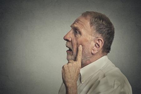 perception: Retrato preocupado hombre de pensamiento que mira para arriba aislado en el fondo gris de la pared con copia espacio. Expresiones faciales humanas, las emociones, los sentimientos, el lenguaje corporal, la percepci�n
