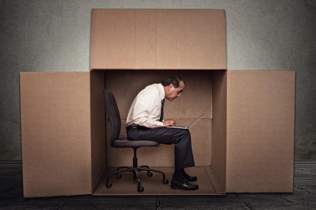 carton: Man sitting in a box working on laptop computer Stock Photo