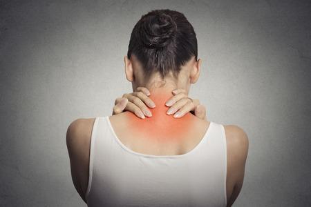 健康的なライフ スタイル。背中や背骨の病気。クローズ アップ バックアップ ビュー疲れ女性赤灰色の背景に分離で彼女の首をマッサージ
