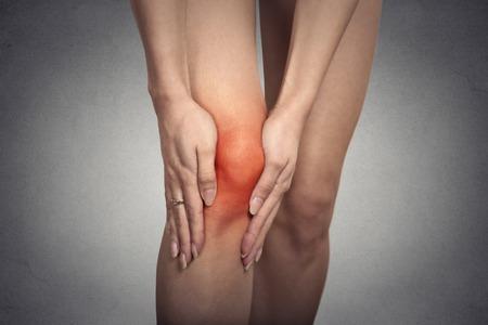 pierna rota: Rodilla tendón de problemas en las articulaciones del primer en pierna de mujer indican con punto rojo sobre fondo gris. Concepto de inflamación de las articulaciones.