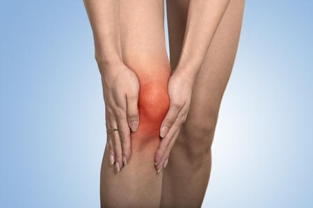 bone fracture: Closeup tendon knee joint problems on woman leg indicated with red spot isolated on blue background. Joint inflammation concept. Stock Photo