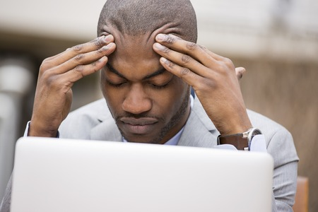 failure: stressed young businessman sitting outside corporate office working on laptop computer holding head with hands looking down. Negative human emotion facial expression feelings.