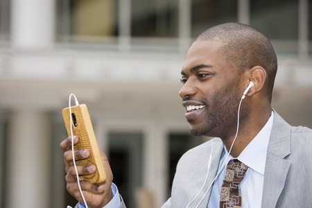 american media: Closeup portrait of a smiling young happy man listening to music on cellphone sitting outdoors on sunny day. Positive face expression