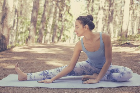 pilate: Stretching woman in outdoor exercise smiling happy doing yoga stretches after running. Beautiful happy smiling sport fitness model outside on summer spring day Stock Photo