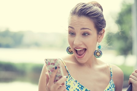 Detailansicht-Porträt überrascht schreien junge Mädchen, das Telefon zu sehen, Nachrichten oder Fotos mit lustigen Emotionen in ihrem Gesicht außerhalb der Stadt Hintergrund. Menschliche Emotion, Reaktion, Ausdruck